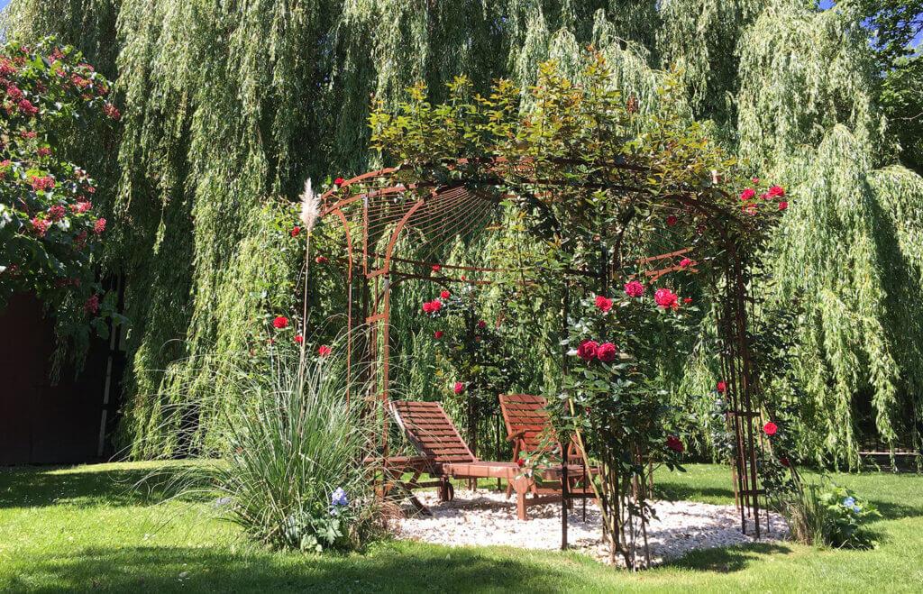 Eindrucksvoll berankter Edelrost-Pavillon mit rot blühenden Kletterrosen